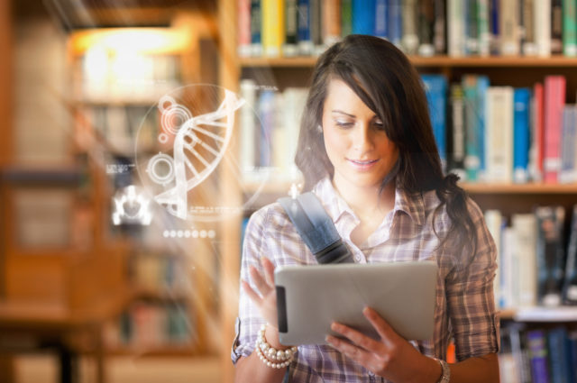 Pretty student using futuristic interface to learn about science from digital tablet standing in college library